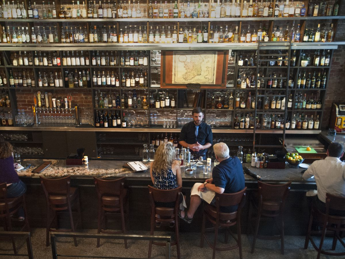 People sit at the bar at Jack Rose Dining Saloon