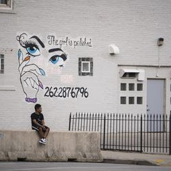 A child sits by himself on a barricade near Civic Center Park on the 5th night of protests after police shot Jacob Blake, a markedly quiet night in the city of Kenosha, Thursday night, Aug. 27, 2020.