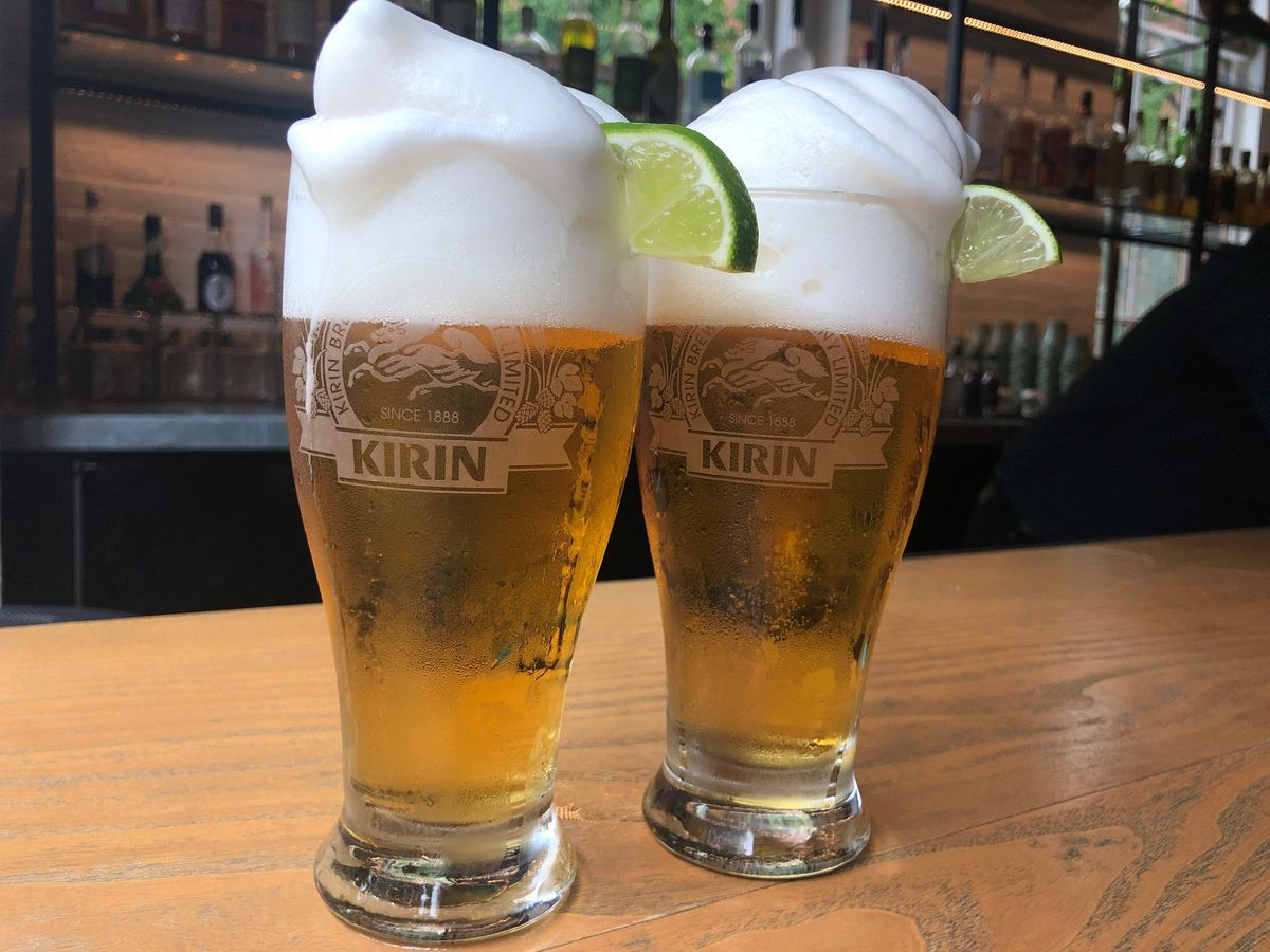 Two Kirin beer slushies, garnished with lime slices, sit on a wooden bar