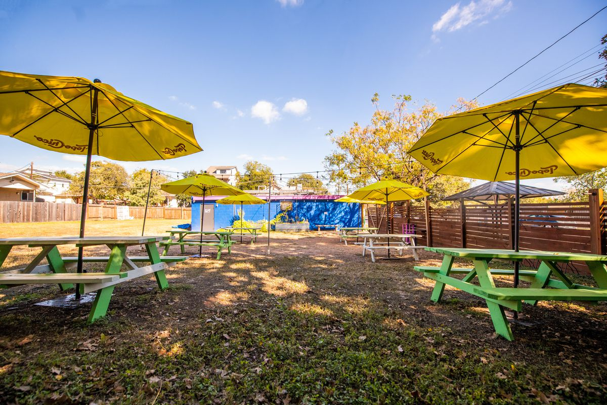 A grassy backyard with two rows of green picnic tables lines vertical with bright yellow umbrellas