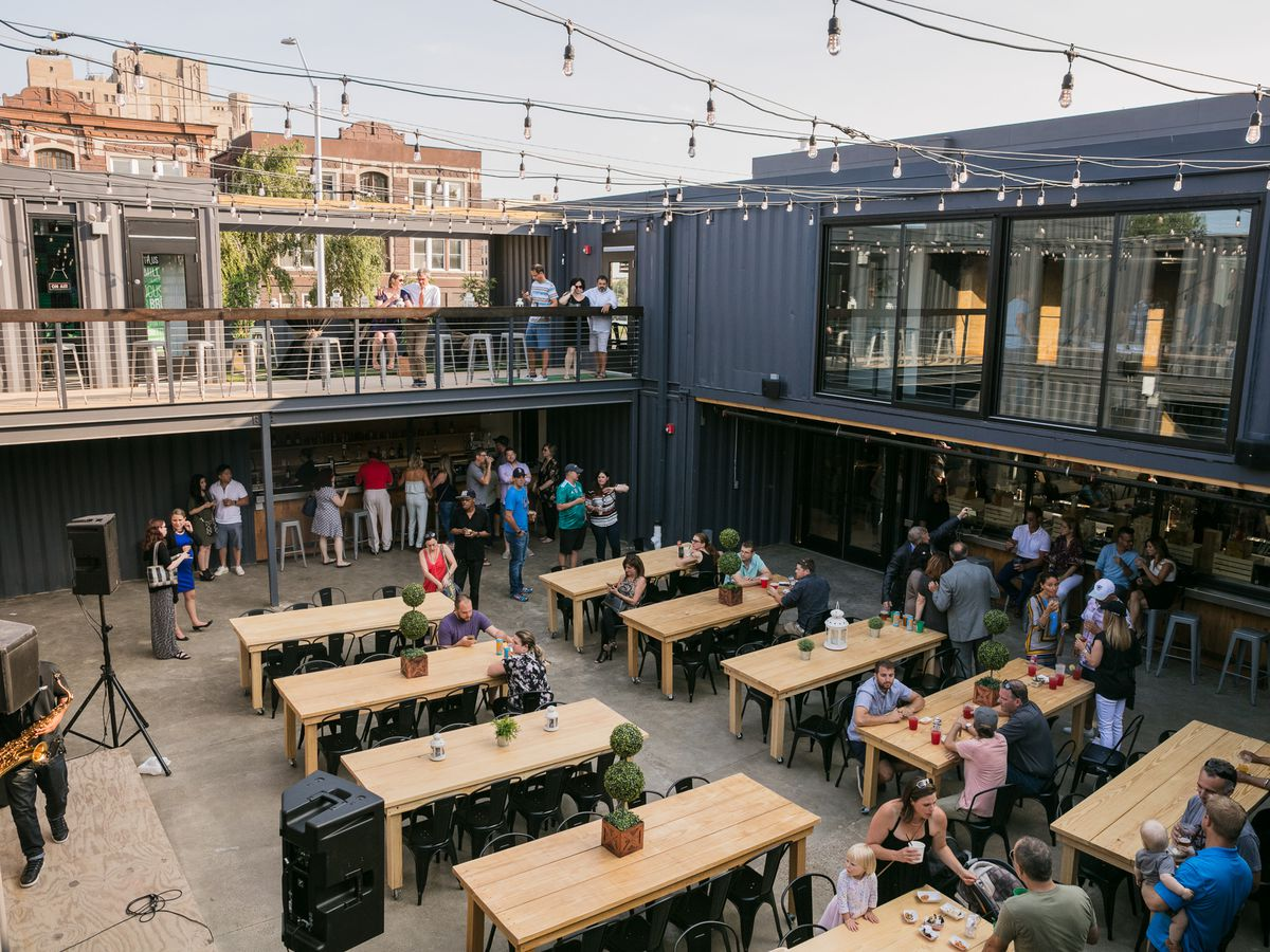 Customers sit at communal tables in an open air courtyard beneath string lights.