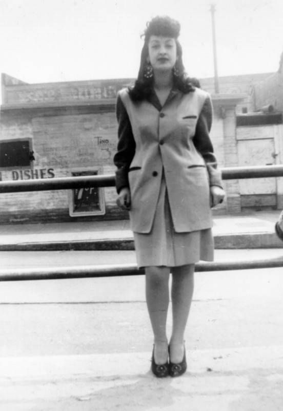 A black and white image of a young women in an oversized, single-breasted blazer, knee-length pencil skirt, and pumps.