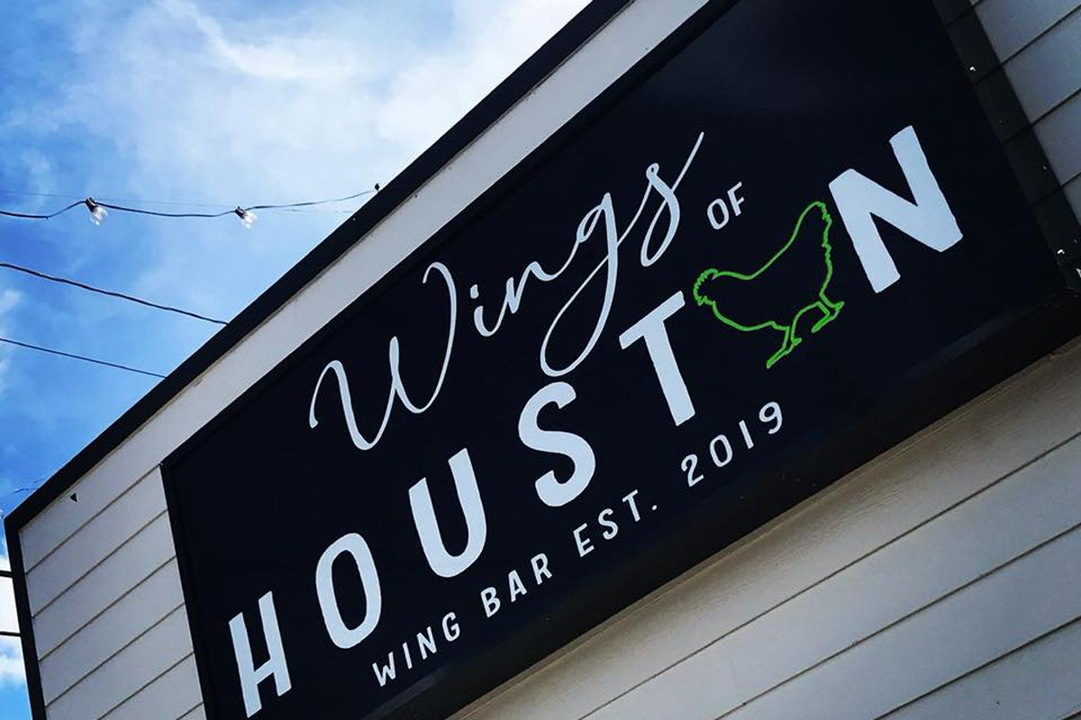 A black sign reading Wings of Houston against a tan wall and blue sky