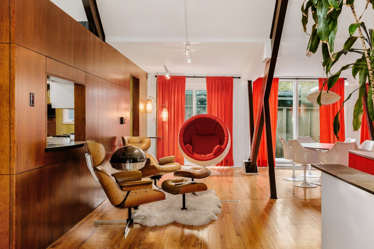Adjacent to the living room there is a seating area with mahogany paneling and Eames-style chairs.