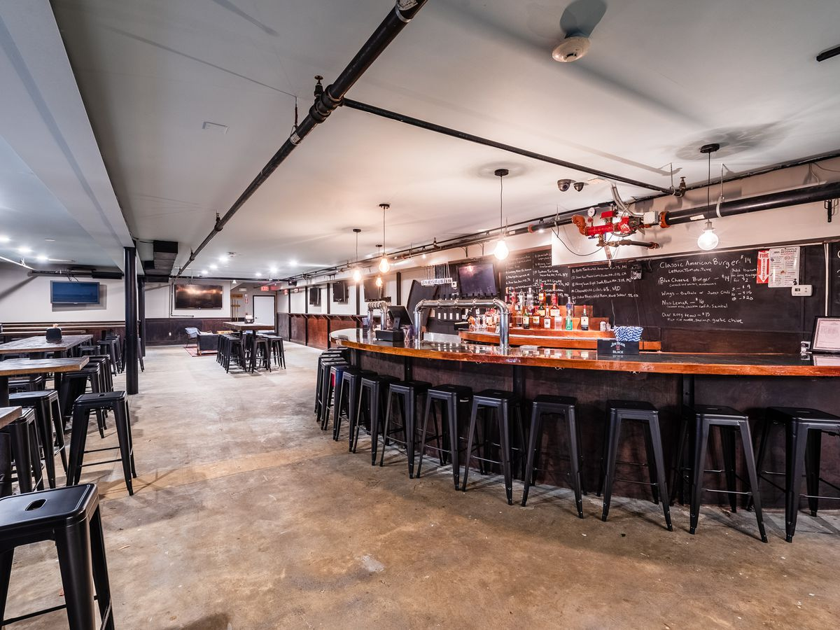 A semicircular bar surrounded by stools at Thirsty Crow