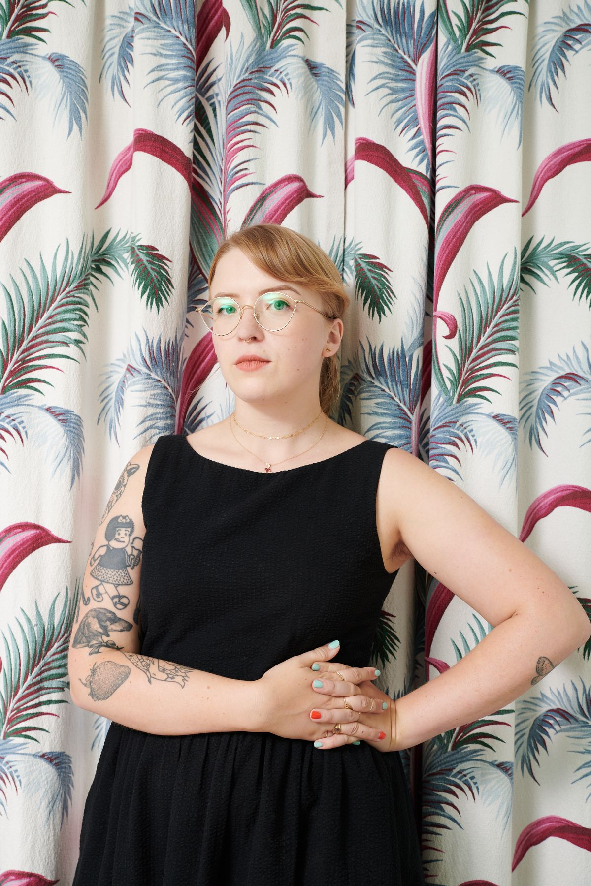 Tuesday Bassen wearing a black sleeveless dress in front of a tropical-themed curtain