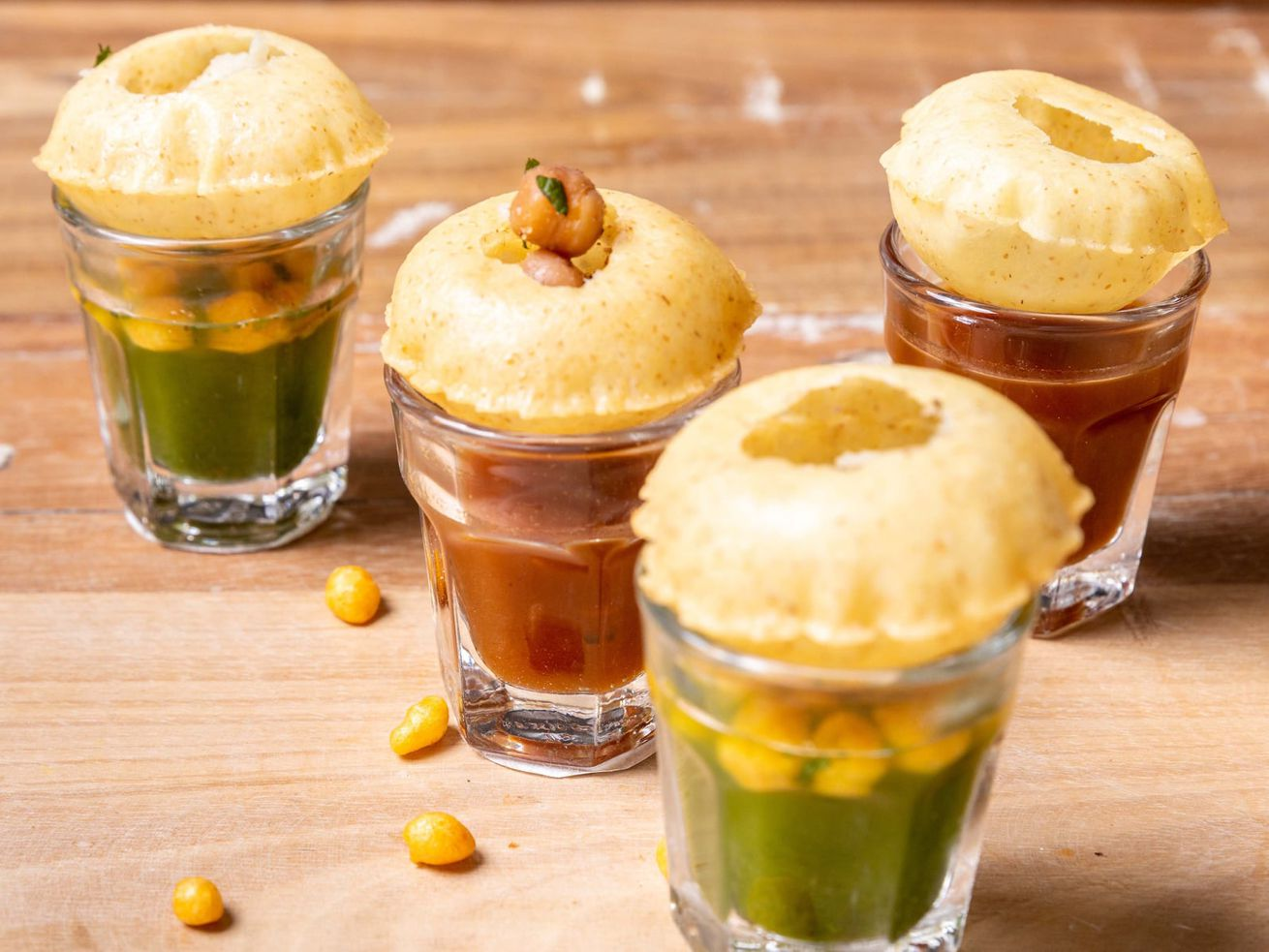 four glasses filled with tamarind and mint flavoured water, with a puri sitting on top of each one