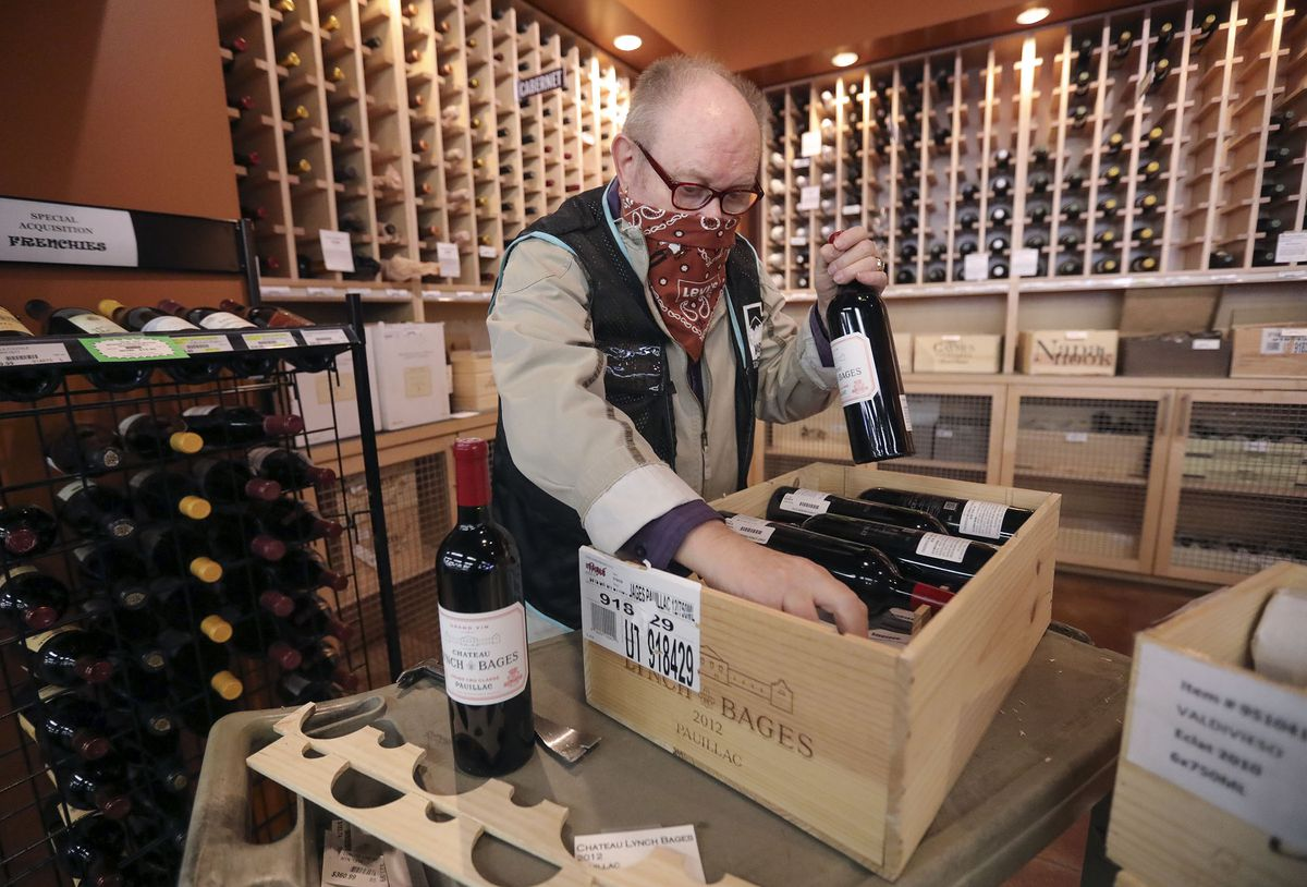 Drew Ellsworth, a part-time clerk, stocks wine at a state liquor store in Salt Lake City on Friday, Oct. 23, 2020.
