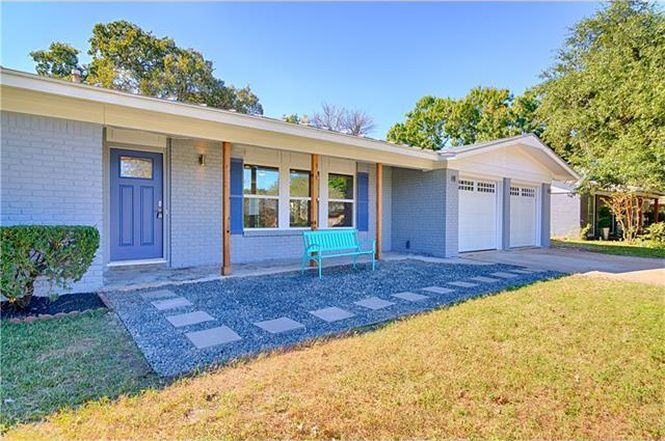 Light-blue brick ranch style house with aqua bench in front