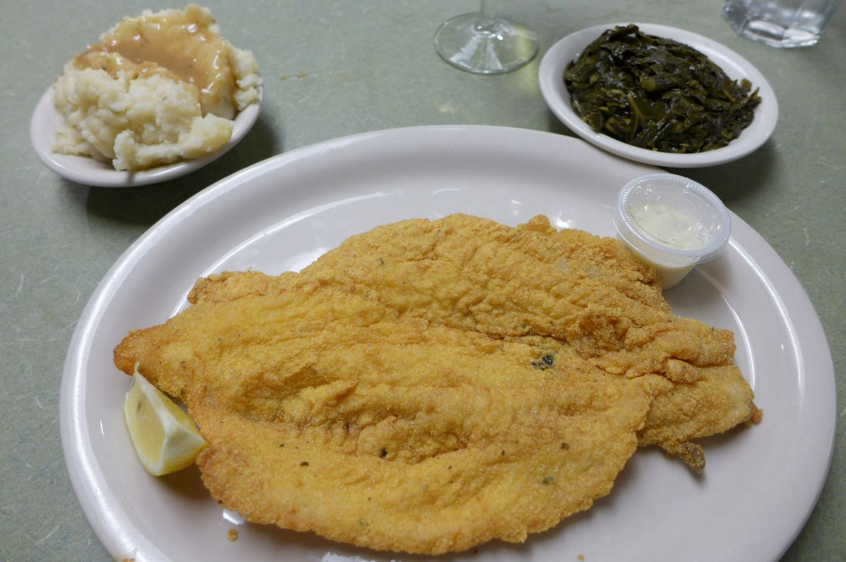 A large breaded fish filet with two side dishes.