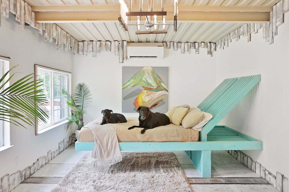 Salvaged wood is used to make an unusual bed whose foot floats above the floor and whose head has a sharp slope. The whole thing is painted aqua and two black dogs (a pit bull named Boomer and a labrador named George) lie on the bed.