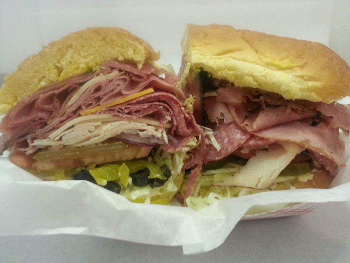 A sandwich sliced in half in a takeout container. The sandwich includes huge portions of sliced beef and turkey, cheese, lettuce, and tomato