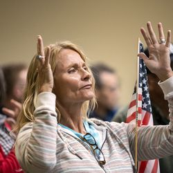 Rebecca Olson uses sign language to applaud after a speaker expressed their opinion about the Biden administration's COVID-19 vaccine mandate during a meeting of the Legislature's Business and Labor Interim Committee at the Capitol in Salt Lake City on Monday, Oct. 4, 2021.
