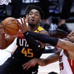 Utah Jazz guard Donovan Mitchell (45) goes up for a shot with Miami Heat forward Andre Iguodala (28) defending as the Utah Jazz and the Miami Heat play an NBA basketball game at Vivint Smart Home Arena in Salt Lake City on Saturday, Feb. 13, 2021.