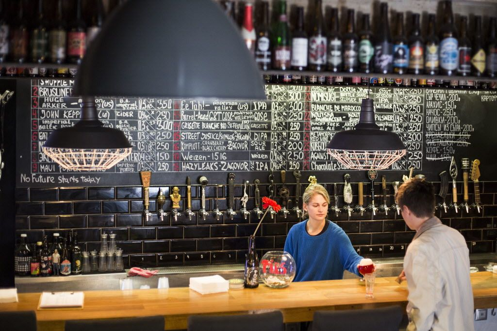 In this July 21, 2017 photo, people enjoy craft beer at the Rule Taproom pub in Moscow, Russia. A new generation of craft beer brewers began sprouting in the vodka capital of the world as foreign beers got too expensive and beer-drinkers started looking f