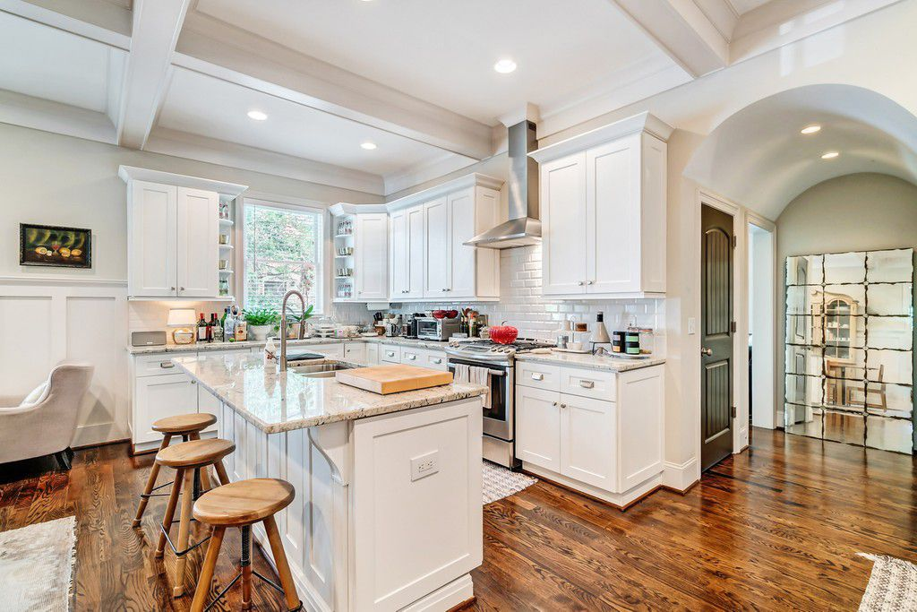 A white kitchen with three stools and coffered ceilings.