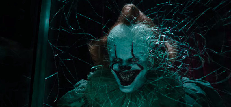 """The scary clown in the movie """"It Chapter Two"""" grins from behind a sheet of shattered glass."""