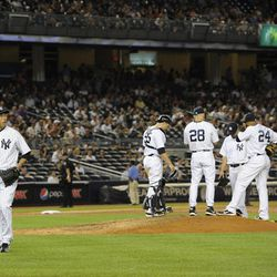 New York Yankees starting pitcher Hiroki Kuroda, left, walks to the dugout after manager Joe Girardi (28) took him out of the baseball game against the Baltimore Orioles, Friday, Aug., 31, 2012, at Yankee Stadium in New York. The Orioles won 6-1.