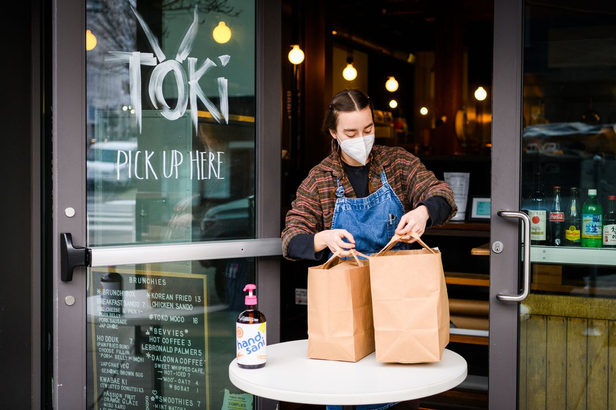 A woman with braids, a mask, and a denim apron brings two paper bags to a small white table in the door of Toki. A bottle of hand sanitizer sits on the table.
