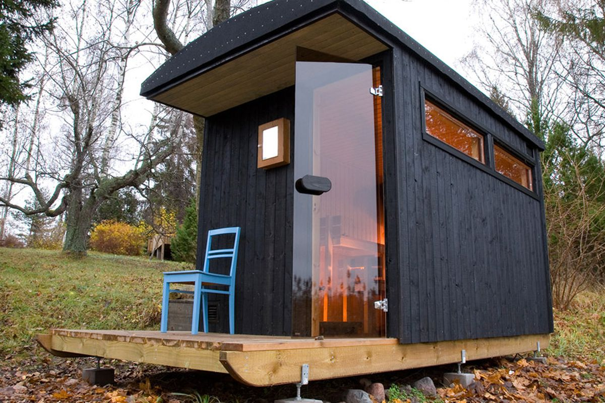 Black wood-clad structure on wooden platform with glass door and small windows sitting on grassy spot.