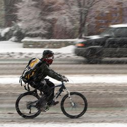 A cyclist pedals across South Temple during an ice storm in Salt Lake City on Thursday, Dec. 19, 2013.