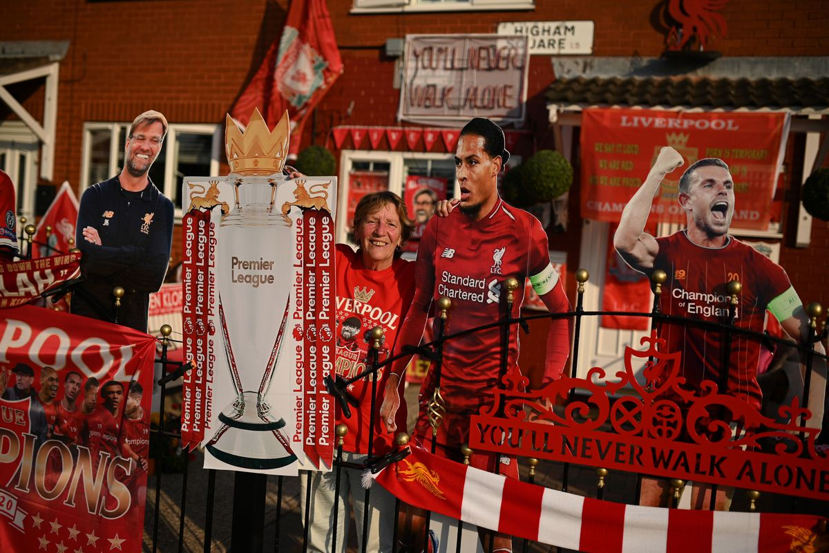 Liverpool fan Emily Farley sits outside her home, decorated with Liverpool banners and cut outs, in Liverpool, north west England on June 25, 2020, as she waits for the result of the match between Manchester City and Chelsea, which gives Liverpool the possibility of taking the Premier League championship.