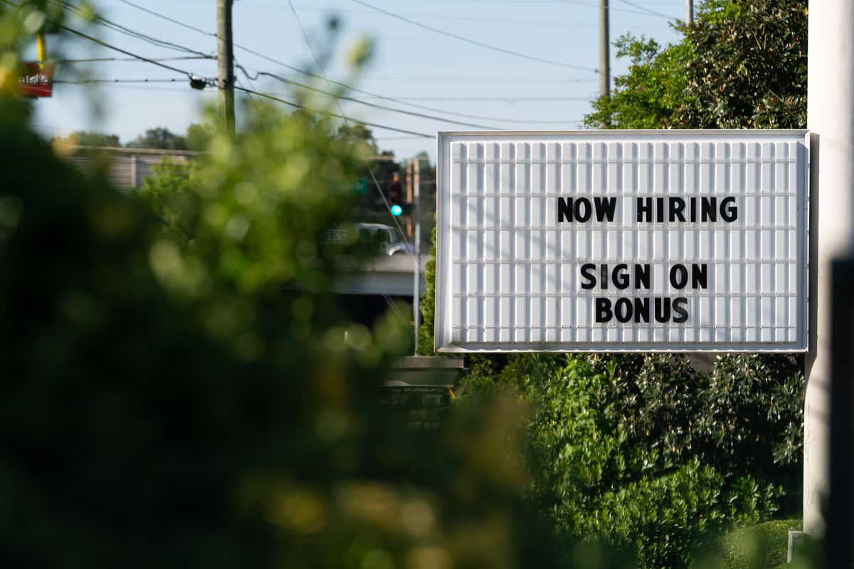 """A sign alongside a road that reads """"NOW HIRING SIGN ON BONUS"""""""