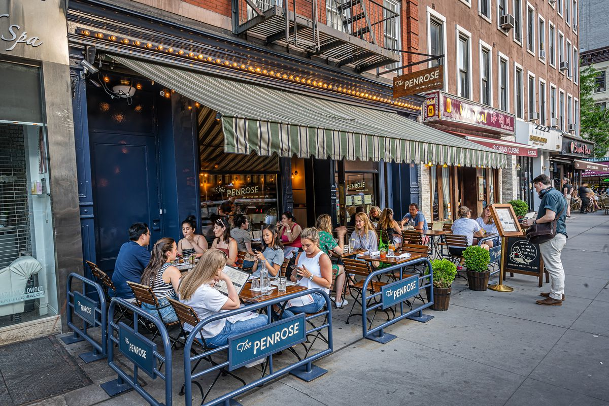 People eating and drinking outside at the Penrose, an Upper East Side Bar