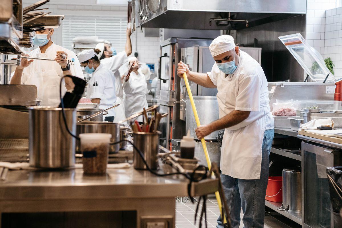 A man wearing a face masks mops the kitchen at Bludorn