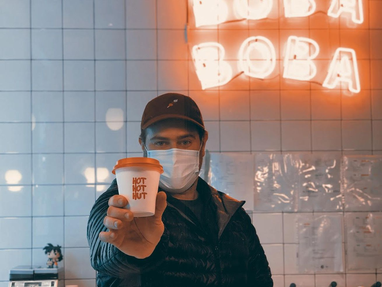 masked man holding takeout coffee cup