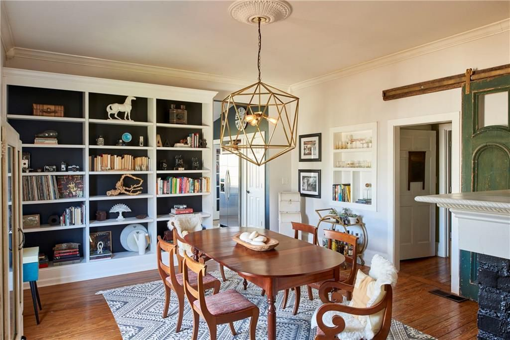 A antique-looking dining room with bookshelves and a long table.