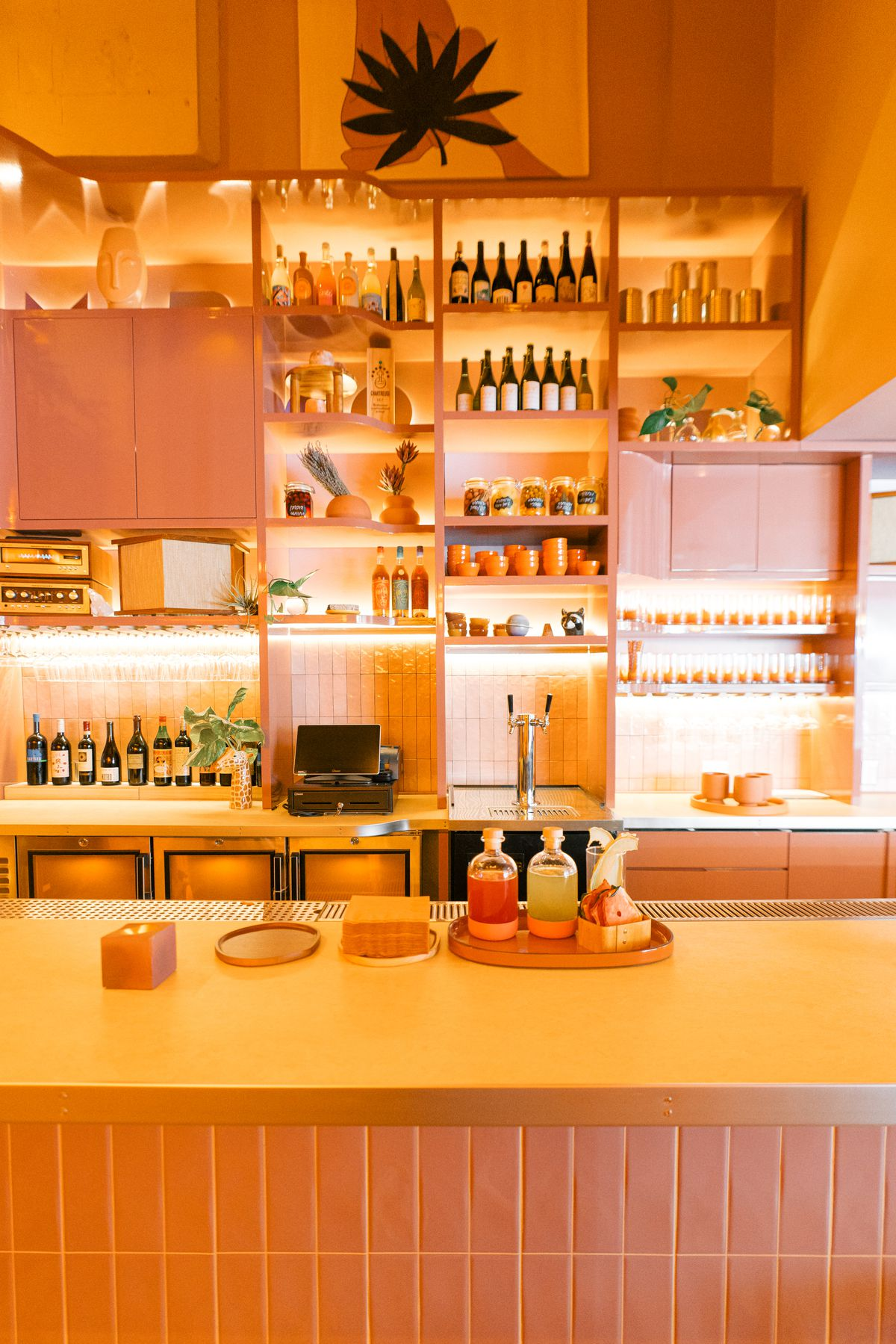 pink bar with eclectic decor and bottles