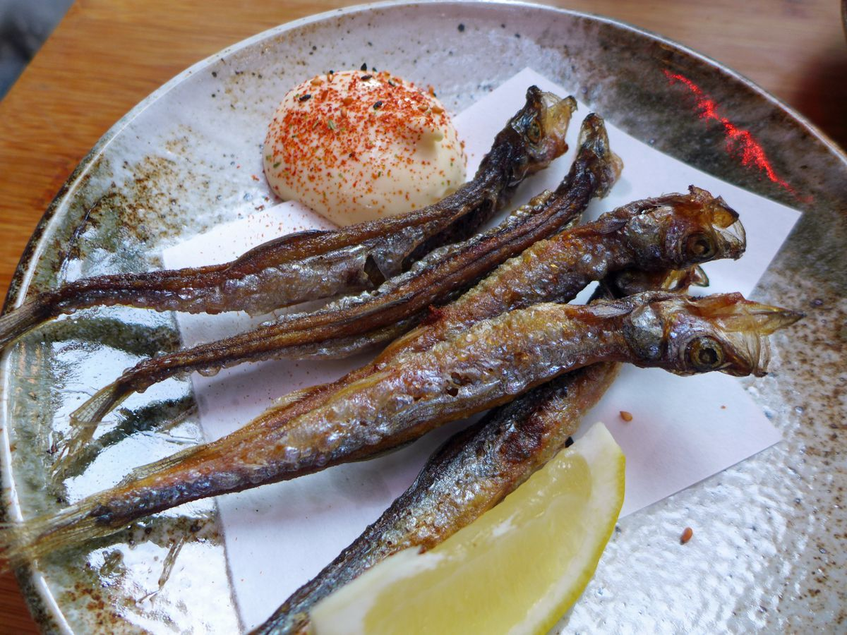 A passel of anchovies glistening on a plate with a lemon wedge and dab of brown mayo dip.