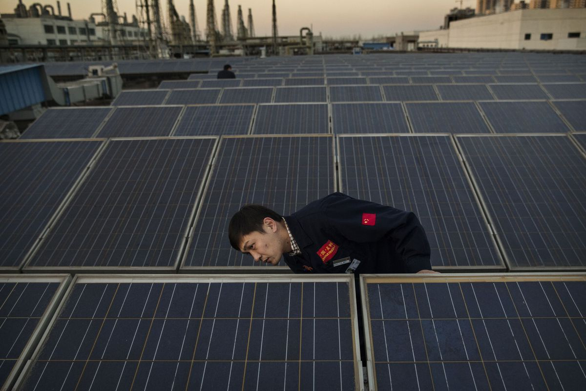 BAODING, CHINA - DECEMBER 4: A manager from Yingli Solar checks a solar panel used to produce energy for lighting, on the roof at the company's headquarters on December 4, 2014 in Baoding, Hebei Province. China is the largest energy consumer in the world