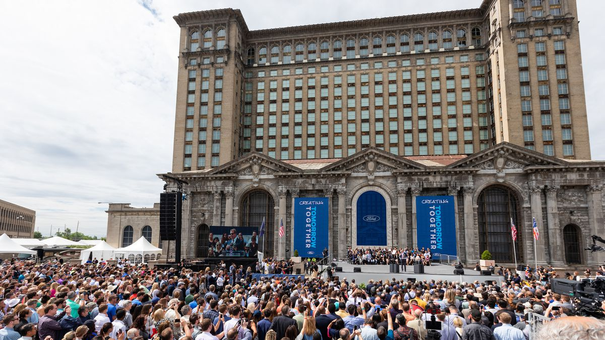 """A large crowd of people gather outside a podium set up in the front of a tall, abandoned and ornate building. Two signs flanking the stage read """"Creating Tomorrow Together."""""""