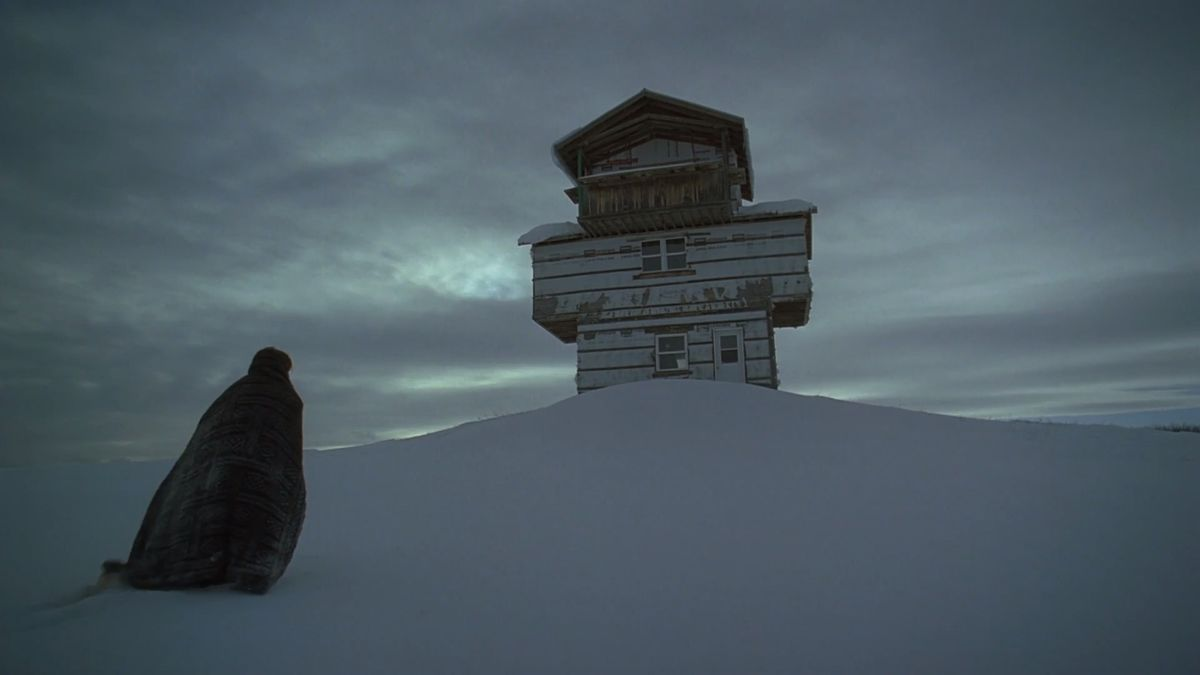 A figure walks in the snow towards a lone building in The Lodge