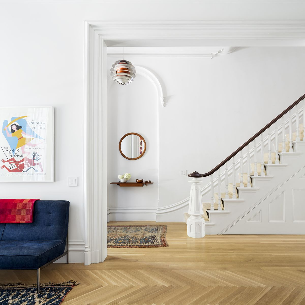 Poul Henningsen's PH Kontrast lamp for Louis Poulsen, now out of production, hangs above an antique mirror and floating shelf by Aksel Kjersgaard in the main entry on the parlor level. The Bucks traded another piece of seating for the Florence Knoll settee.