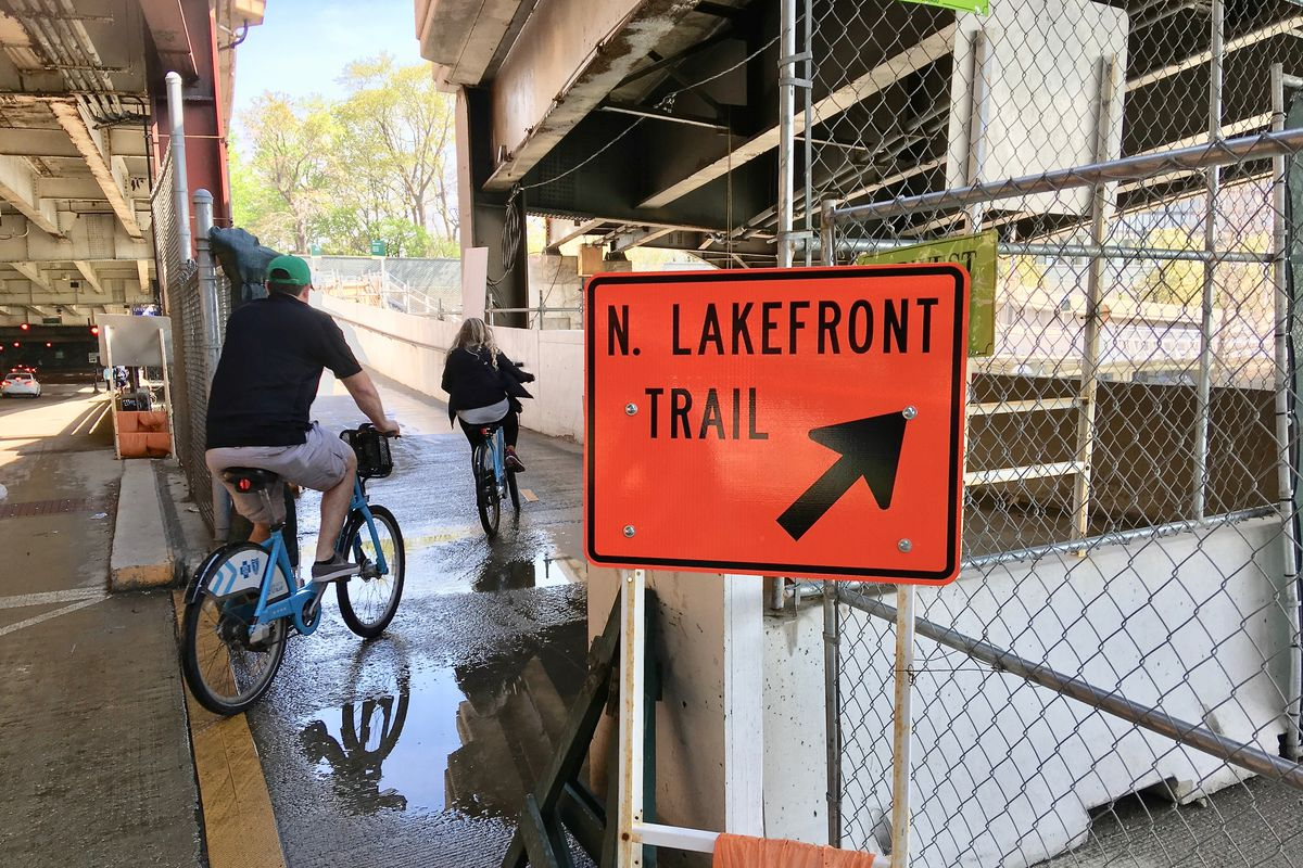 """Two cyclists on a sidewalk beneath a bridge ride onto a ramp with a sign reading """"N. Lakefront Trail."""""""