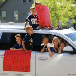 Family of Janet Coleman drive into the parking lot as residents at The Ridge Cottonwood senior living center in Holladay watch as family members parade with signs, balloons and waves for Mother's Day on Saturday, May 9, 2020.