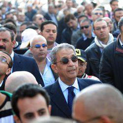 FILE - In this Nov. 28, 2011 file photo, Egyptian presidential hopeful Amr Moussa, center, waits outside a polling station before voting on the first day of parliamentary elections in Cairo, Egypt. The presidential election scheduled in May will mark the beginning of a handover of power by the ruling military to an elected civilian, following last year's popular uprising that overthrew Hosni Mubarak. (AP Photo/Hossam Ali, File)