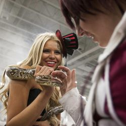 Karalee Bugden pets a snake that is held by Hannah Cockrell during Salt Lake Comic Con at the Salt Palace Convention Center in Salt Lake City, Thursday, Sept. 4, 2014.