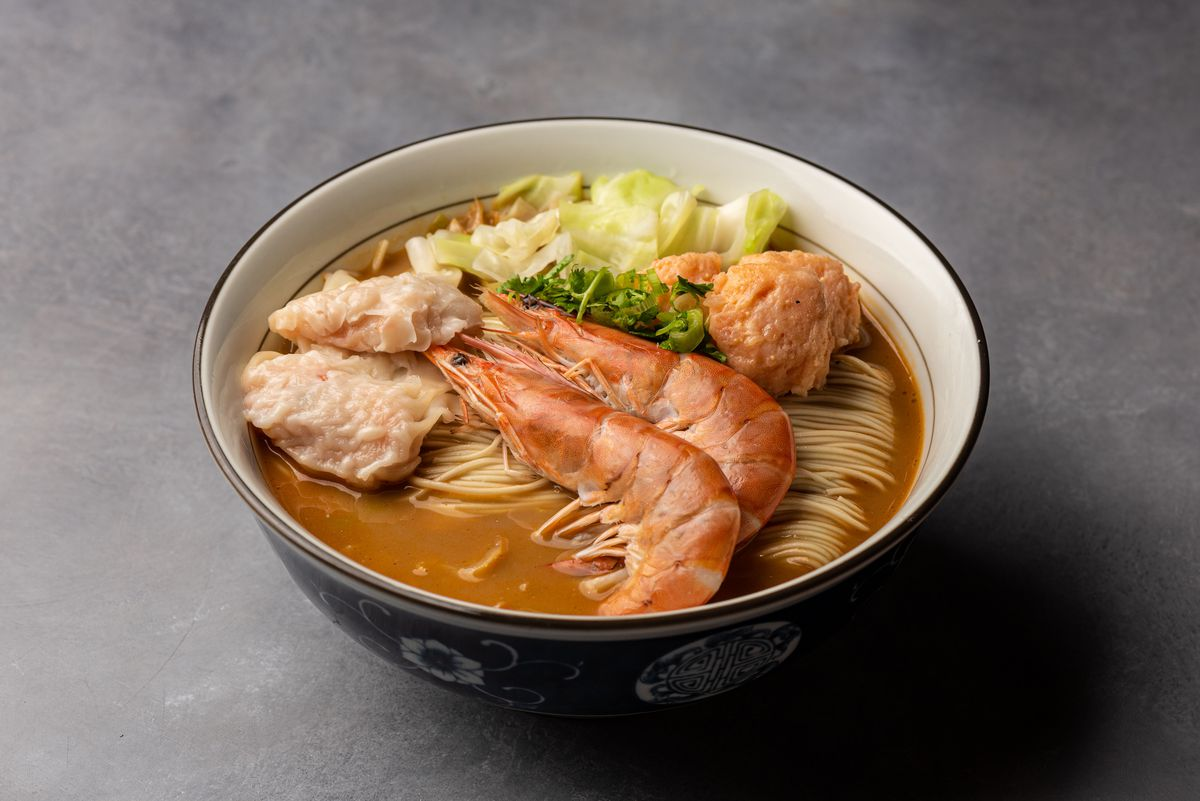 Two shrimp, meatballs, and noodles in a bowl of soup.