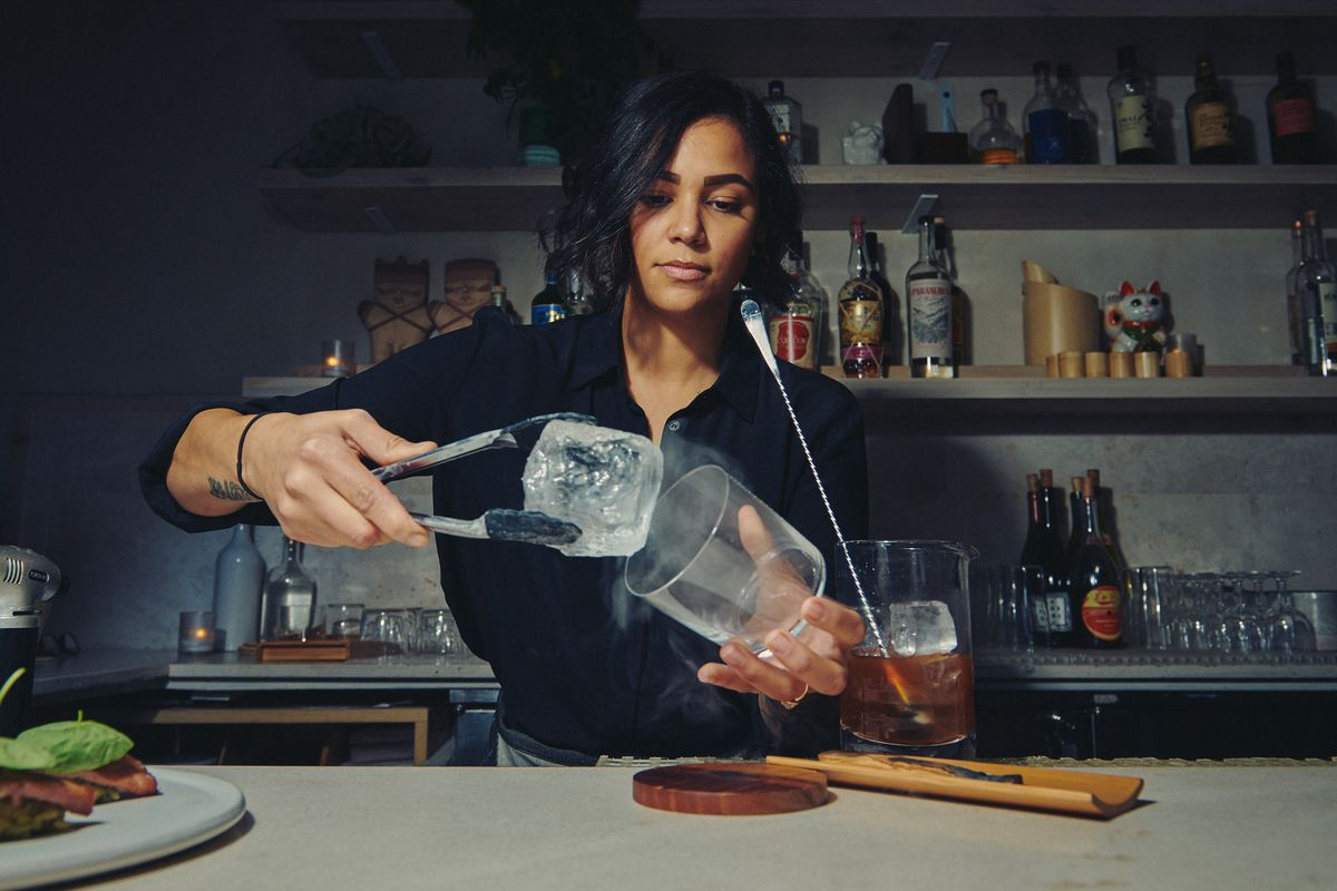 A bartender places an ice cube into a glass filled with palo santo smoke, while a brown cocktail awaits pouring