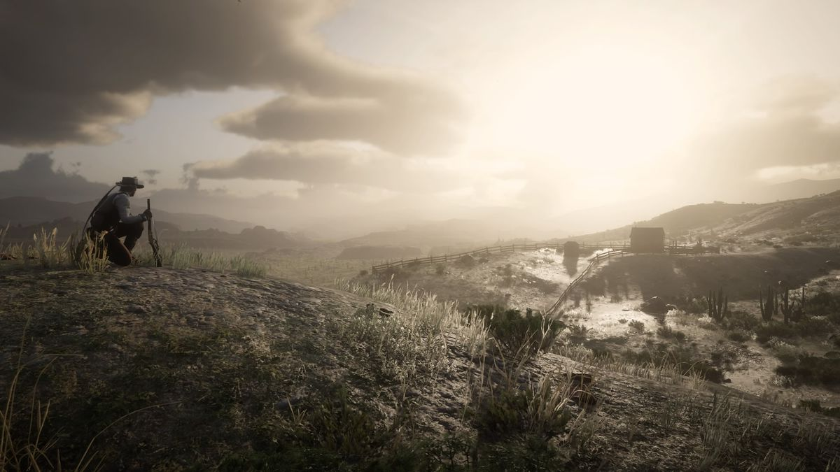 A cowboy sits on a hill out in the wilderness