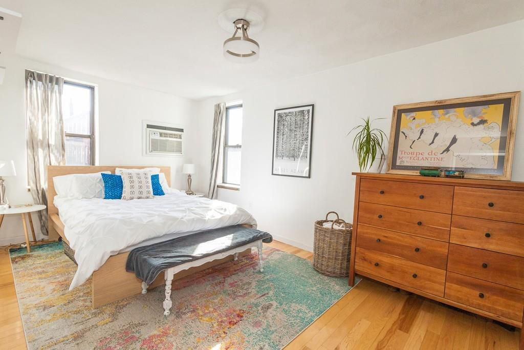 A sunny bedroom with a bed, a bench at the end of the bed, and a dresser next to that.