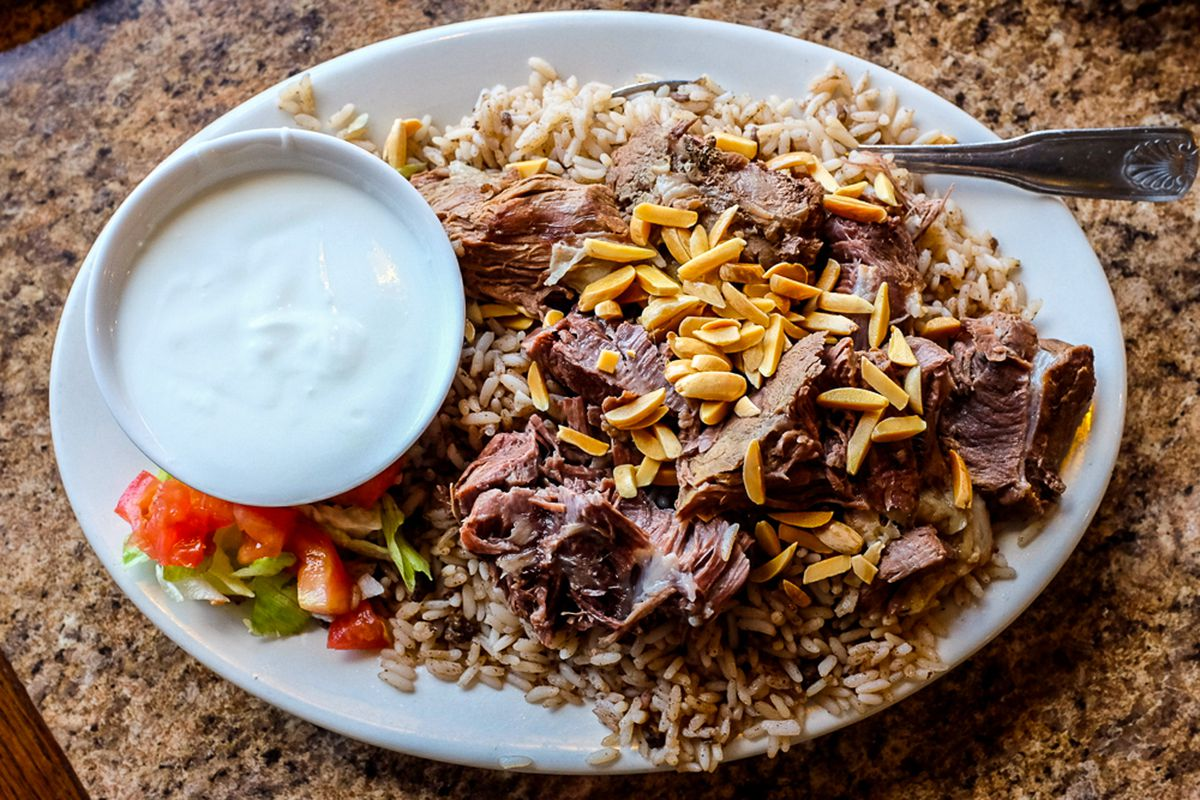 A large plate of rice with stuffed lamb pulled into pieces on top and sprinkled with slivered almonds. A large dish of creamy white sauce sits on the plate next to some cubed tomatoes.