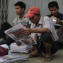 A Myanmar newspaper hawker reads a newspaper featuring pro-democracy leader Aung San Suu Kyi a day after landmark by-elections in Yangon, Myanmar, Monday, April 2, 2012. Suu Kyi, 66, was elected to parliament Sunday in a historic victory buffeted by the jubilant cheers of supporters who hope her triumph will mark a major turning point in a nation still emerging from a ruthless era of military rule.
