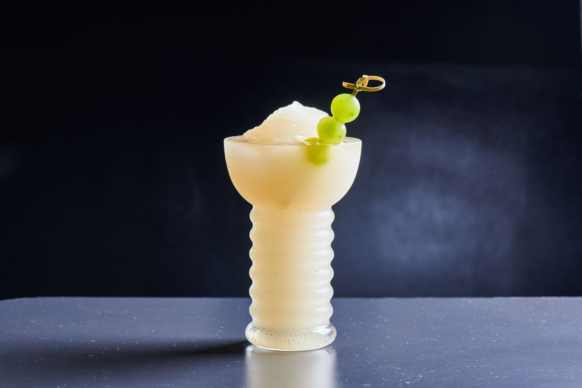 A frozen drink stands in a tall cocktail glasses with a skewer of three green grapes
