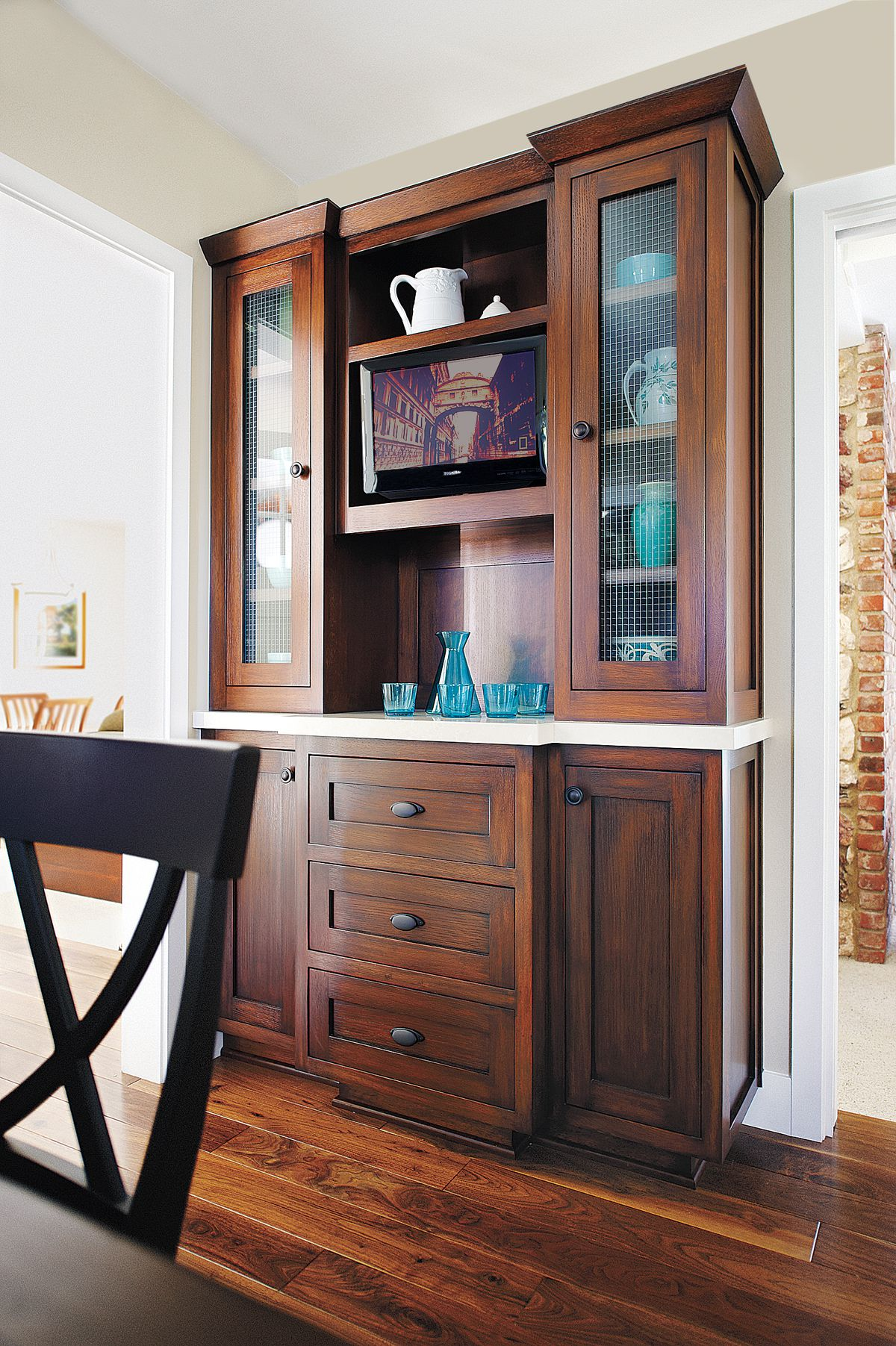 Wooden dining room cabinet with a quartz countertop built in.