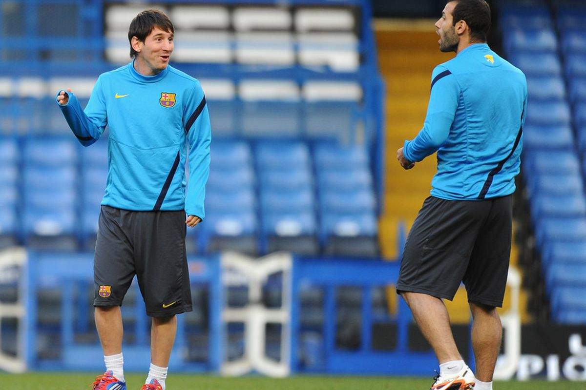 Lionel Messi of Barcelona shares a joke with team-mate Javier Mascherano during a training session ahead of their UEFA Champions League semi-final first leg match against Chelsea at Stamford Bridge on April 17, 2012 in London, England.